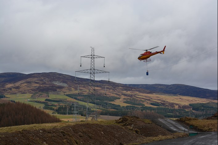 A helicopter stringing towers near Fort Augustus during construction of the Beauly-Denny line