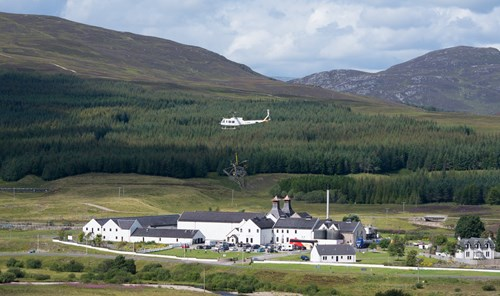 A helicopter carrying part of a transmission tower flies past Dalwhinnie Distillery in the Cairngorms National Park